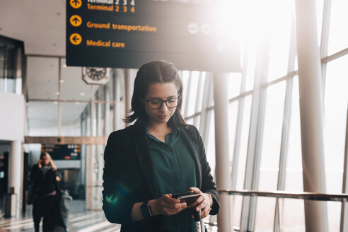 Mid adult businesswoman using mobile phone while standing in airport terminal - MASF07823