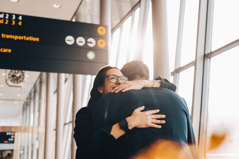 Smiling businesswoman embracing businessman at airport terminal - MASF07826