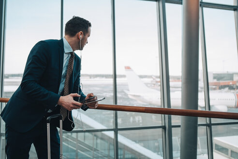 Businessman looking at airplane through window while using mobile phone in airport - MASF07847