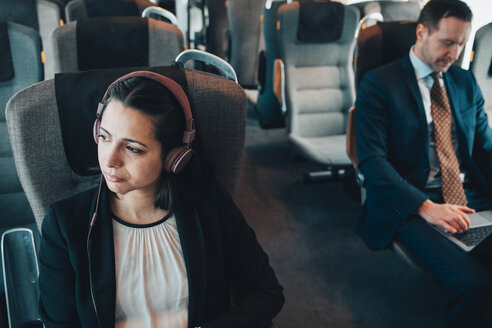 Businesswoman using headphones while traveling with businessman in train - MASF07853