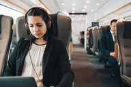 Mid adult businesswoman using headphones and laptop while traveling in train - MASF07856