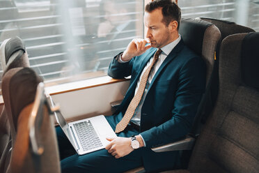 High angle view of businessman using laptop while traveling in train - MASF07859