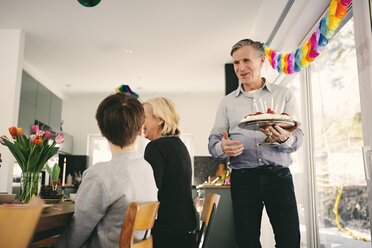 Boy looking at grandfather holding birthday cake in party - MASF07925