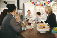 Family sitting at table during birthday party - MASF07931