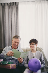 Smiling grandfather reading greeting card while sitting with grandson and gifts at party in living room - MASF07949