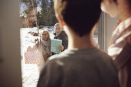 Siblings looking at happy grandparents through window - MASF07952