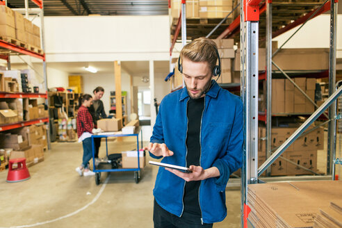 Confident man using digital tablet while leaning on rack with coworkers working in background - MASF07958