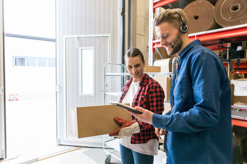 Smiling man showing digital tablet to female coworker holding box in distribution warehouse - MASF07961