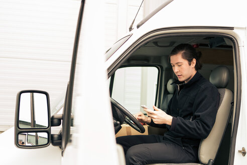 Side view of manual worker using mobile phone while sitting in delivery van - MASF07973