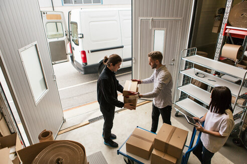 High angle view of male coworkers delivering boxes while female is using digital tablet - MASF07976