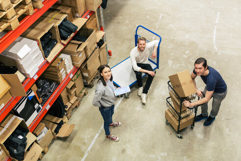 High angle portrait of male and female coworkers in distribution house - MASF07985