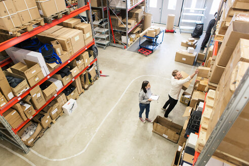 High angle view of coworkers examining boxes on rack in industry - MASF07988