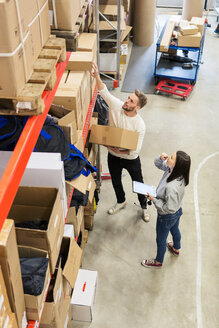 High angle view of colleagues examining boxes in industry - MASF07991
