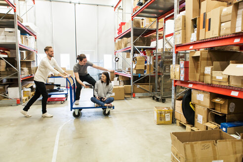 Coworkers enjoying while working at warehouse - MASF07994