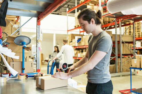 Manual worker packing box while coworkers discussing in distribution warehouse - MASF07997