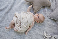 Portrait of baby girl, wrapped in blanket, overhead view - CUF20943