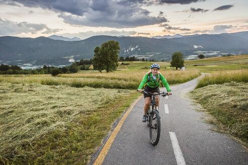 Woman cycling on road, Fondo, Trentino, Italy - CUF20955