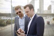 Two businessmen on footbridge texting on smartphone, London, UK - CUF21006
