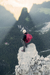 BASE jumper checking the exit spot at Torre Trieste, Italian Alps, Alleghe, Belluno, Italy - CUF21015