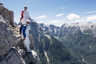 BASE jumpers getting ready to jump together from cliff, Italian Alps, Alleghe, Belluno, Italy - CUF21021