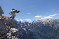 Wingsuit BASE jumper getting ready to jump from cliff, Italian Alps, Alleghe, Belluno, Italy - CUF21024
