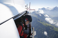 Female sky diver in helicopter checking for exit over mountain, Interlaken, Berne, Switzerland - CUF21027