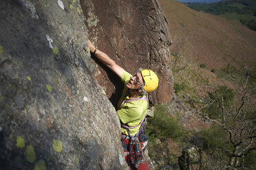 High angle view of rock climber climbing rock face - CUF21045