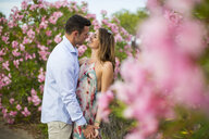 Romantic couple dancing together by blossoms, Majorca, Spain - CUF21102