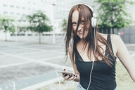 Portrait of young woman listening to headphones and dancing outside office building - CUF21132