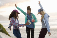 Three young female friends dancing together on beach, Cape Town, Western Cape, South Africa - CUF21204