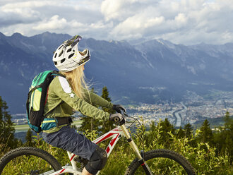 Austria, Tyrol, female downhill mountain biker looking into valley - CVF00637