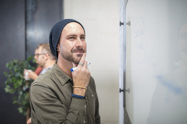 Young man thinking at whiteboard in office - ZEF15529