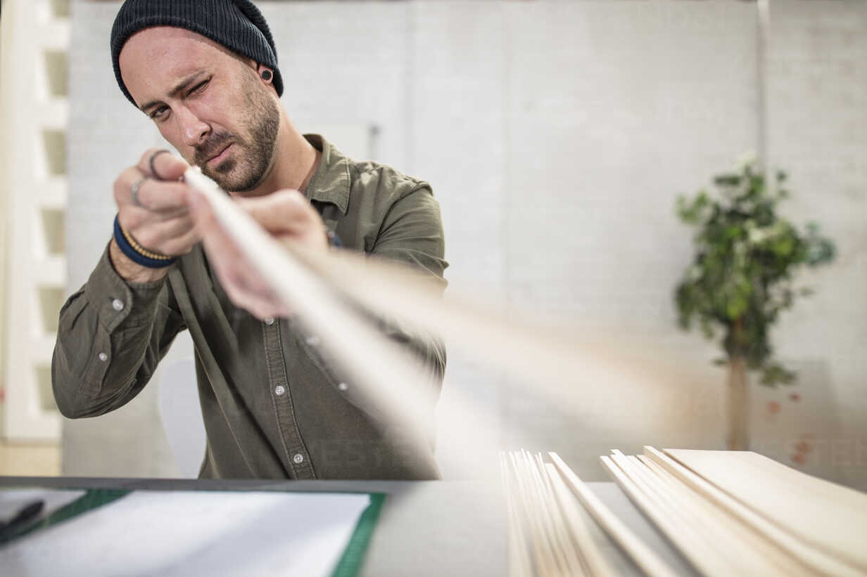 Young man working with wood at desk in office - ZEF15544 - zerocreatives/Westend61
