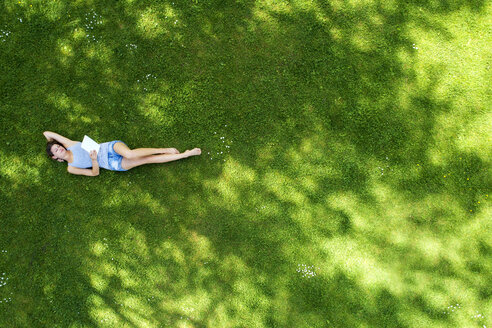 Young woman lying on meadow, using tablet - MAEF12610