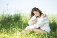 Smiling young woman sitting on meadow - MAEF12622
