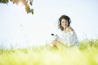 Smiling young woman with earphones and smartphone listening to music - MAEF12625