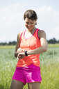 Smiling young woman having a break from exercising looking on smartwatch - MAEF12643