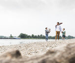 Happy father with two sons and football walking at the riverside - UUF13914