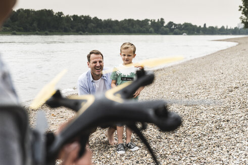Happy father with two sons playing with drone at the riverside - UUF13920