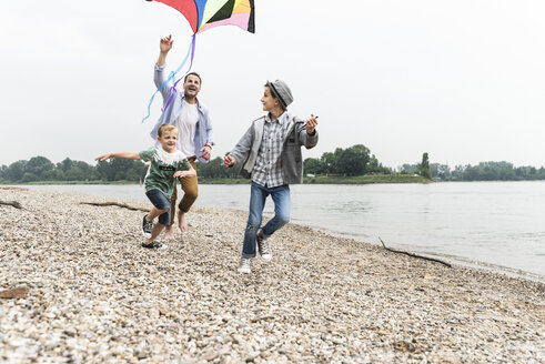 Happy father with two sons flying kite at the riverside - UUF13923