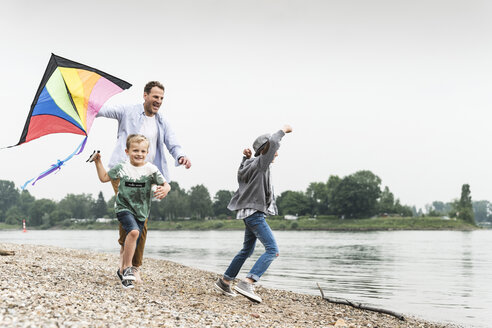 Happy father with two sons flying kite at the riverside - UUF13929