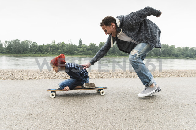 Happy father pushing son on skateboard at the riverside - UUF13938 - Uwe Umstätter/Westend61