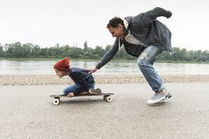 Happy father pushing son on skateboard at the riverside - UUF13938