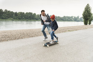Happy father running next to son on skateboard at the riverside - UUF13941