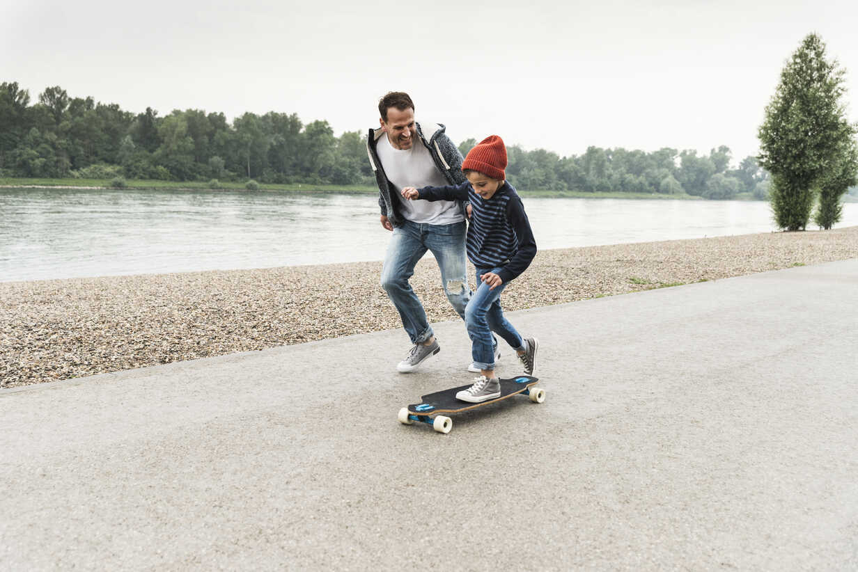 Happy father running next to son on skateboard at the riverside - UUF13941 - Uwe Umstätter/Westend61