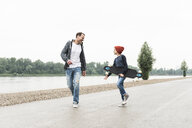 Happy father and son with skateboard at the riverside - UUF13944