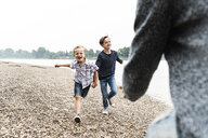 Happy boys running towards father at the riverside - UUF13953