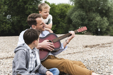 Father with two sons sitting on pebble beach playing guitar - UUF13956