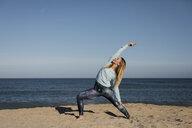 Woman doing yoga on the beach - MAUF01429
