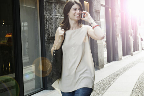 Woman using smartphone whilst strolling on traditional street, Milan, Italy - CUF21241